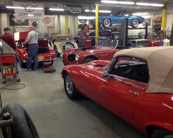 An MGB gets attention while a Jaguar E type and Austin Healey await their turn.