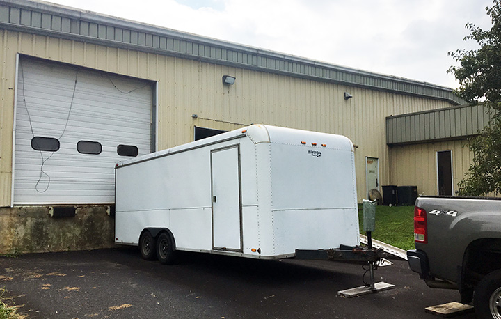 Our white 20-foot trailer at the shop loading dock, ready to go.