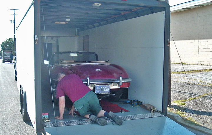 Ken Beck prepares to unload a 1969 Jaguar XKE coming into the shop on a K&T trailer.
